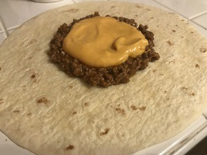 Spread cheese sauce over ground beef
