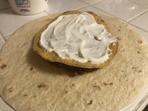Spread sour cream over the tostada shell